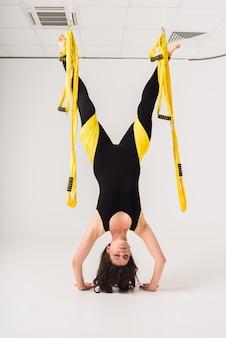 垂直方向のスポーツウーマンは、白い壁に黄色いハンモックで逆立ちを行います
