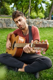 Vertical outdoor portrait of handsome hipster guy sitting on grass in park and playing guitar