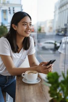 Tシャツ、ジーンズ、無駄のないコーヒーテーブルで陽気な美しい若い現代アジアの女の子を垂直屋外ショット。