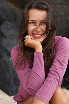 매력적인 여자의 세로 야외 촬영은 길고 검은 머리카락, 긍정적 인 표정을 가지고 있습니다.