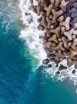 Ripresa aerea aerea verticale di un mare blu ondulato contro le rocce