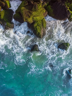 Vertical overhead aerial shot of a wavy blue sea against the rocks