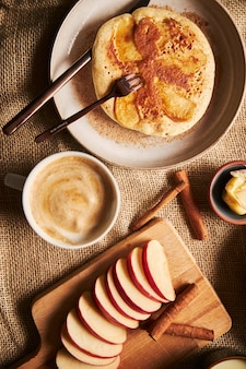 Vertical overhead shot of apple pancakes with apples coffee cinnamon and butter on the side