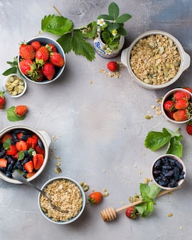 Vertical overhead shot of bowls filled with oats, strawberries and blue fruits