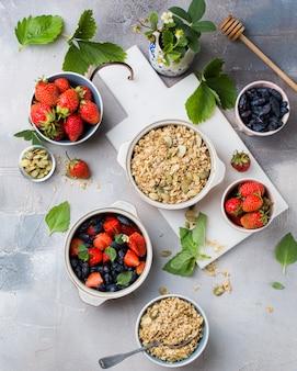 Colpo ambientale verticale di ciotole piene di avena, fragole e frutti blu