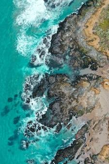 푸른 깨끗한 물과 모래 해변과 바다의 아름다운 해안선의 수직 오버 헤드 샷