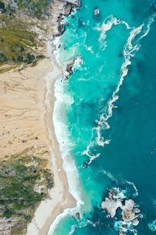 Вертикальный вид сверху на красивую береговую линию моря с голубой чистой водой и песчаным пляжем