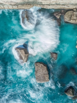 Vertical overhead shot of rock formations on the body of blue sea
