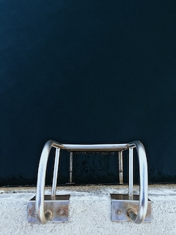 Vertical overhead shot of a silver ladder in a pool