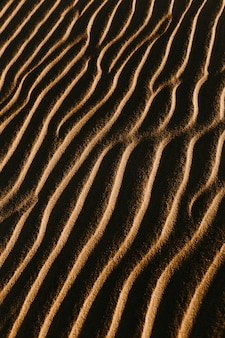 Colpo sopraelevato verticale della sabbia ondulata con il sole che splende su esso