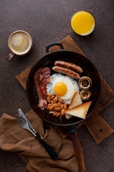 Vertical pan fried english breakfast on wooden background traditional american cuisine