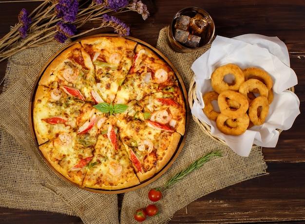 세로 사진과 말린 꽃, 차가운 음료, 나무 테이블에 튀긴 양파와 함께 자루천에 있는 맛있는 수제 해산물 피자를 닫습니다. 음식과 음료 개념입니다.