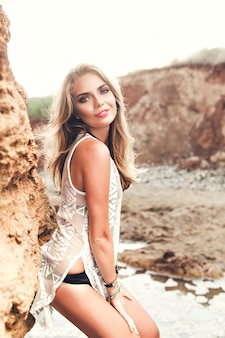Vertical photo of attractive blonde girl with long hair  posing to the camera on rocks background. she is smiling.