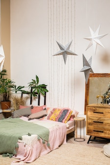 Vertical photo of a bedroom decorated with plants and garlands and with a large double bed with colorful blanket