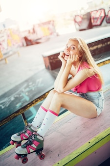 Vertical photo of blonde model wears rollers and shorts with blouse