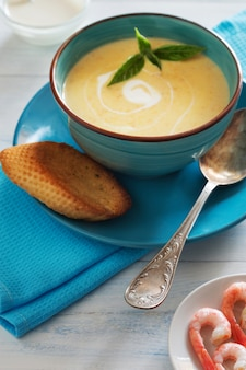 Vertical photo of bowl of cream soup with shrimps, basil and bread