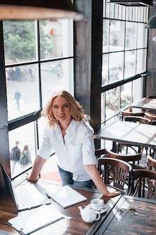 縦写真。昼間のカフェで室内に金髪の巻き毛を持つ実業家。