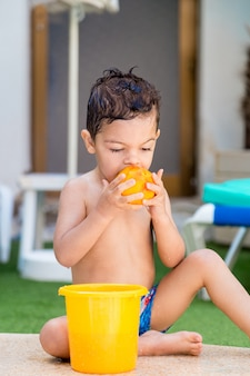 Vertical photo of a caucasian child sitting on the ground at the edge of a pool eating fruit