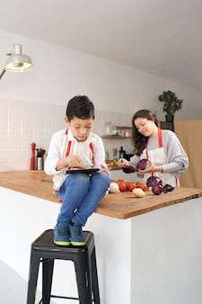 세로 사진입니다. 어머니가 야채를 요리하는 동안 태블릿을 가지고 노는 부엌에서 앞치마를 입은 아이. 건강한 식생활.
