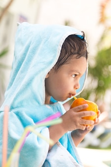 Vertical photo of a child with a hooded towel facing forward while eating fruit