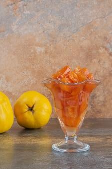 Foto verticale di mele cotogne fresche con marmellata