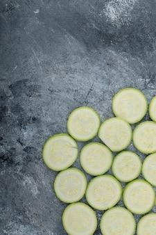 Vertical photo of fresh sliced zucchini slices.