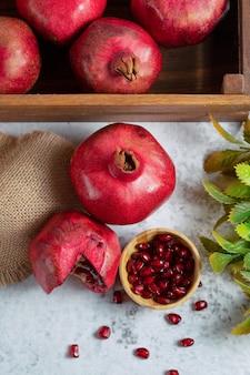 Foto verticale di cassetta di frutta e melograni freschi.