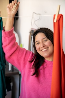 Vertical photo of a girl with a pink sweater and long hair hanging out clothes