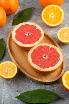 Vertical photo of half cut grapefruits on wooden board over grey surface.