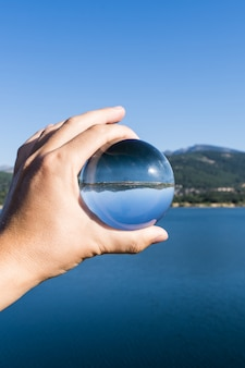 Vertical photo of a hand of a person holding a crystal ball reflecting the landscape of a lake with mountains in a water reservoir in navacerrada in the sierra in madrid