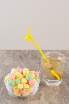 Vertical photo of homemade colorful candies with cocktail on grey.