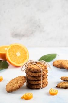 Foto verticale di biscotti fatti in casa e arancia tagliata a metà con foglie sul muro bianco.