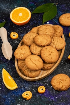 Vertical photo of homemade fresh cookies and cookie with orange over space surface.
