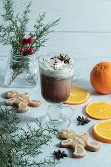 Foto verticale di gelato, biscotti e fette di arancia su bianco.