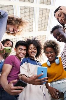 Вертикальное фото под низким углом зрения группы молодых подростков, держащих мобильные телефоны