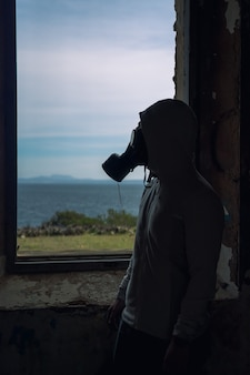 Vertical photo of a man in a gas mask in front of a window inside an abandoned building