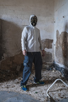 Vertical photo of a man wearing a gas mask inside an abandoned building
