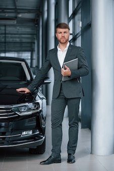 Vertical photo. modern stylish bearded businessman in the automobile saloon