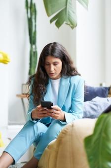 Вертикальное фото красивой латинской бизнес-леди, пьющей кофе в красивой современной квартире с ...
