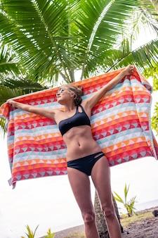 ヤシの木の前でカラフルな布を持ち上げているビキニのブロンドの女性の垂直写真