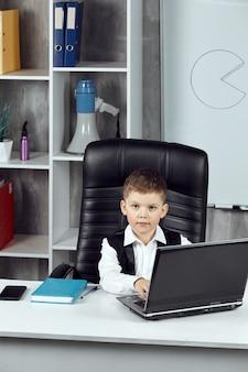 사무실의 감독 책상에 앉아 있는 소년의 세로 사진