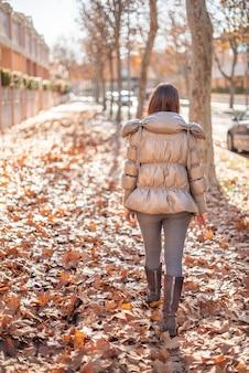 落ち葉でいっぱいの通りを歩いている冬服を着た白人女性の垂直写真