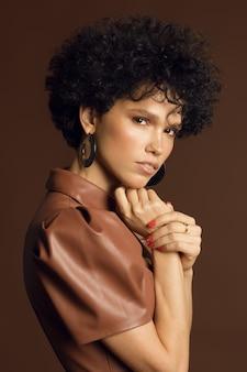 茶色の色調のスタジオでの縮れ毛の女性モデルの垂直写真。高品質の写真
