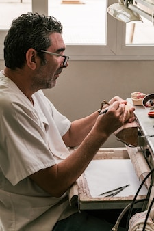ワークショップで働く歯科技工士の縦の写真。