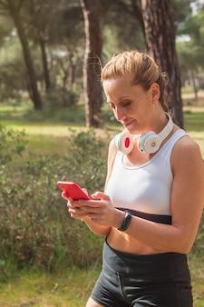 스포츠를 연습하고 헤드폰으로 음악을 들으며 소셜 미디어에서 스마트폰을 사용하는 피트니스 여성의 세로 사진. 건강한 생활.