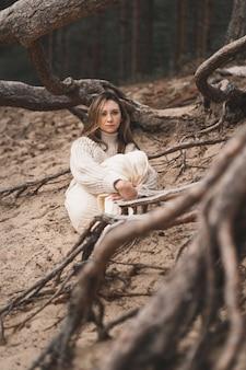자연 속에서 가벼운 스웨터를 입은 갈색 머리가 나무 뿌리 사이에 앉아 있는 세로 사진...