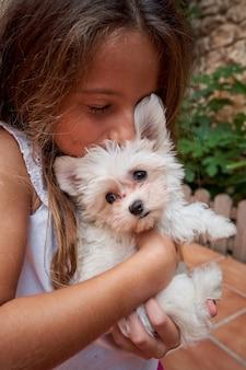 그녀의 팔에 안고 있는 작은 흰색 개와 키스하는 소녀의 세로 사진