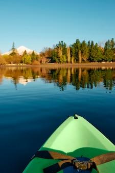 Вертикальное фото зеленого каяка посреди тихого озера в окружении естественного леса и заснеженного вулкана