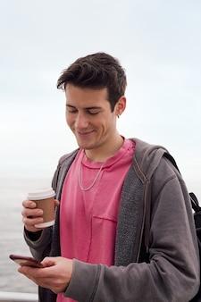 커피 한 잔을 들고 웃고 휴대폰을 사용하는 행복한 젊은 남자의 세로 사진