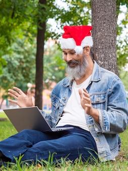 Вертикальное фото мужчины средних лет с ноутбуком в парке, сидящего на траве в новогодней шапке ...